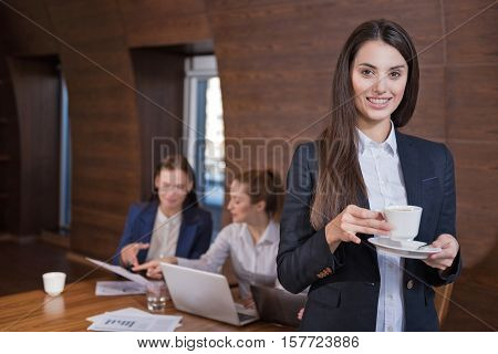 We are so beautiful. Young pretty ambitious woman posing while her colleagues working and sitting in an office.