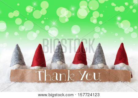 Label With English Text Thank You. Christmas Greeting Card With Gnomes. Sparkling Bokeh And Green Background With Snow And Stars.