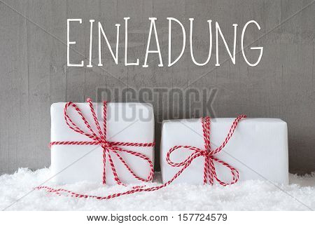 German Text Einladung Means Invitation. Two White Christmas Gifts Or Presents On Snow. Cement Wall As Background. Modern And Urban Style.