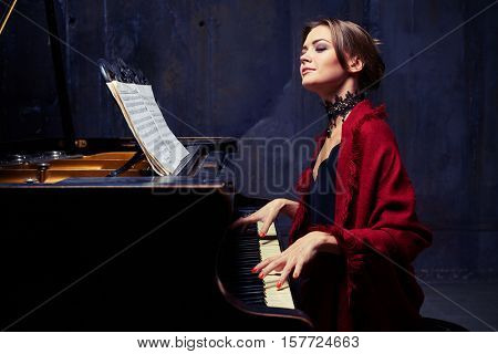 Side mid shot of delighted young woman who is making coherent sounds on the piano, enjoying the unity of melody and harmony. Wearing eveningwear with red scarf and lace black necklace
