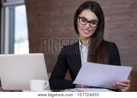 Concentrated and professional. Beautiful young delighted woman wearing glasses and reading documents while working in office with a laptop.