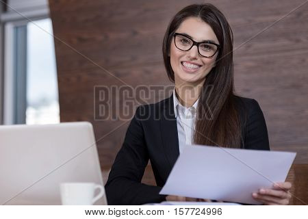 Good skills. Young pretty delighted woman working in an office and wearing glasses while reading documents.