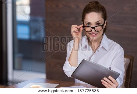 Pretty and official. Joyful young beautiful woman wearing glasses and using tablet while working in an office.