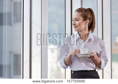 How to be inspired. Pretty young delighted woman enjoying coffee break while spending time at her workplace and relaxing.