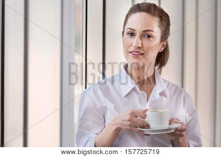 Happy workday. Joyful young pretty woman enjoying coffee break while spending time in cozy office after working.