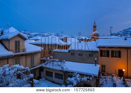 Houses covered with snow in evening in Piedmont, Northern Italy.