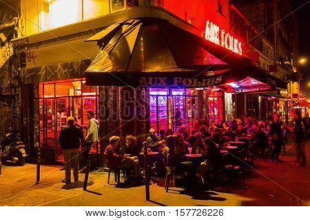 Paris France - October 17 2016: cafe bar in Belleville with unidentified people at night. Belleville is a colourful multi-ethnic neighbourhood and also home to one of the citys two Chinatowns
