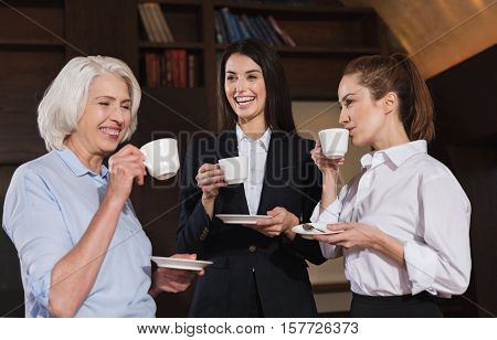 Funny conversation. Amused female friendly colleagues drinking coffee while having break and talking in an office.