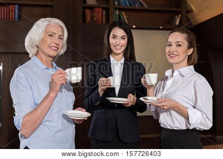 Pretty women. Female joyful elegant colleagues posing while having coffee break and talking in an office.