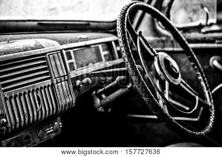 Grunge and hight rusty old car. Black-white photo.