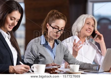 All day long. Three female concentrated colleagues doing their job while noting and using laptop and cellphone in an office.