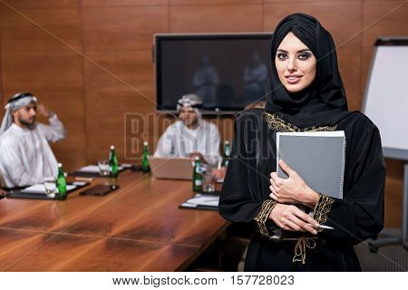 Good job. Smiling pretty Muslim woman standing in the conference hall wearing black hijab and holding a grey folder and a pen in both hands