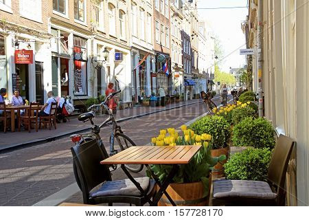 AMSTERDAM, NETHERLANDS - MAY 8, 2016: Typical street in The Nine Streets - special neighbourhood is full with vintage and designer shopping speciality stores and cozy cafes, Amsterdam.