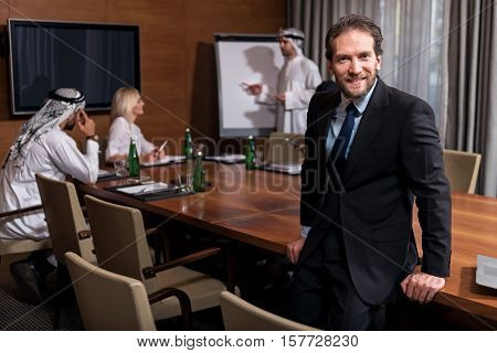 Feel the progress. Positive delighted bearded man leaning against the table wand conducting the conference while two Arabic men speaking with a secretary in the background.