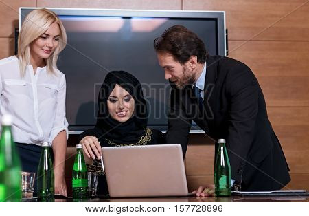 Board of directors. Three professional positive young people discussing important information using the laptop in the oconference hall