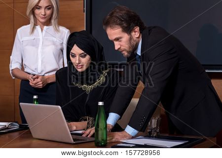 Look into the laptop. Young pretty business woman in black robe sitting between secretary and manager using the laptop while working together