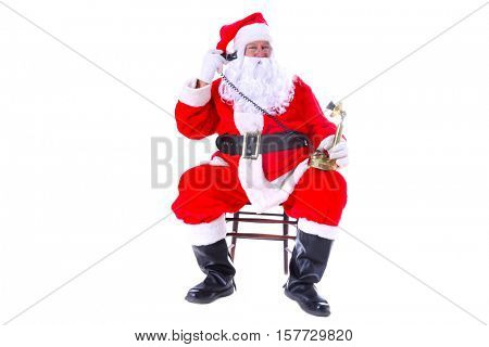 Santa Claus talks to good boys and girls on his telephone while at the North Pole before Christmas Eve. Isolated on white with room for your text.
