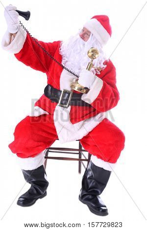 Santa Claus tries to take SELIFE PHOTOS with his Old Fashioned Candlestick telephone while at the North Pole before Christmas Eve. Isolated on white with room for your text.