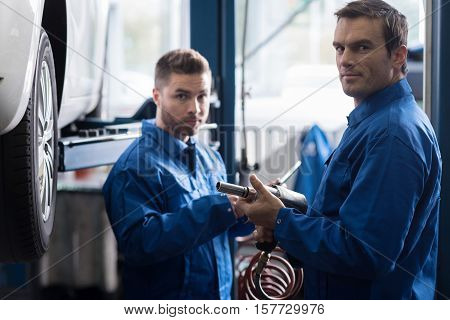 I know what to do. Professional adult car machanic holding pneumatic wrench and changin wheel while his colleague standing in the background