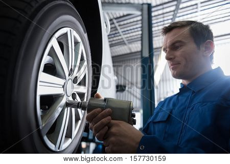Magic hands. Professional serious mechanic using pneumatic wrench and changing wheel while workign with hisc olleague in auto service