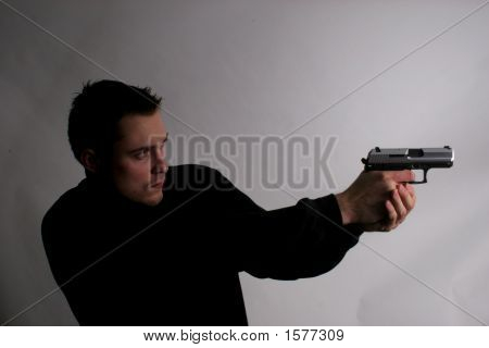 Man Pointing Gun To The Right In Dark Area