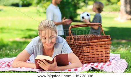 Father and son playing football while the mother is reading
