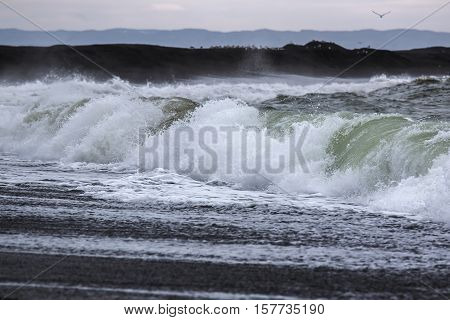 beautiful wave of the sea falls on black beach