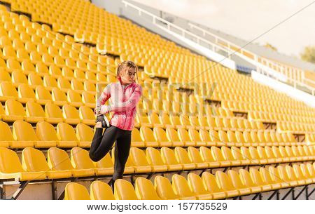 Portrait of a sports woman doing warm up exercises at stadium