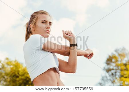 Portrait of a fitness woman doing warm up exercises outdoors