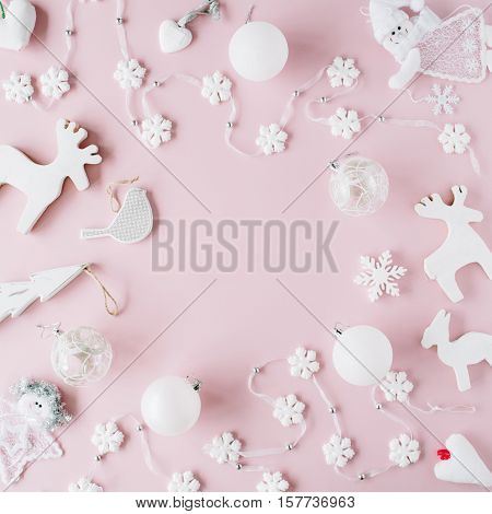 frame made of white christmas decoration with christmas glass balls tinsel bow elk bird on pink background. christmas wallpaper. flat lay top view