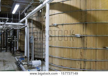 Oak fermenting tanks inside bourbon distillery factory.