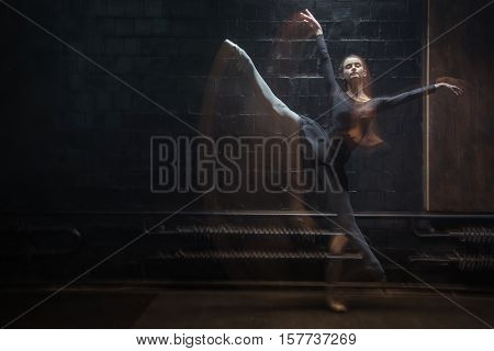 Dancer in motion. Involved graceful young dancer jumping in the twine while raising her hands and being in motion