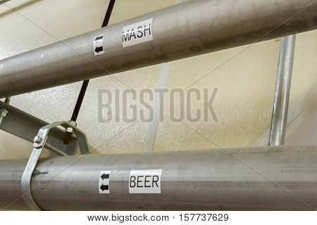 Inside modern fermentation room with pipes for mash and beer in bourbon distillery.