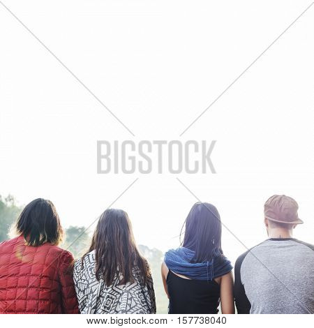 Friends Sitting in a Row Outdoors Concept