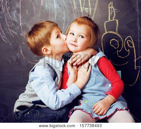 little cute boy kissing blonde girl in classroom at blackboard, first school love, lifestyle people concept close up