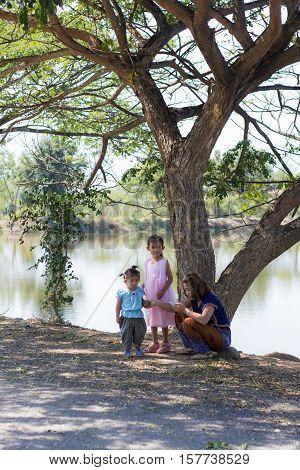 family with tree near lagoon , asian