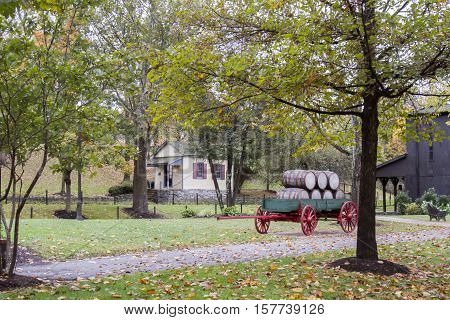 Bourbon barrels on wagon in tree lines countryside of Kentucky in fall.