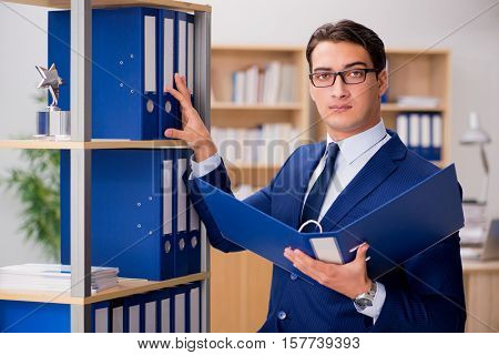 Handsome businessman standing next to shelf