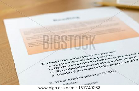 english reading test sheet on wooden table