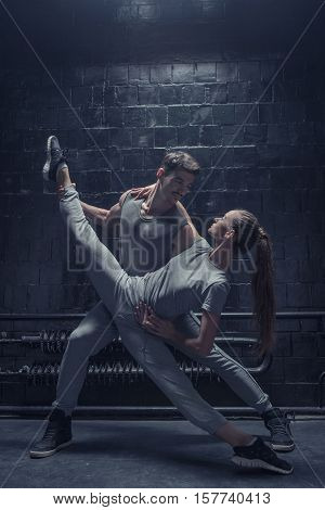 Amazing flexibility. Flexible concentrated young dancer making a twine while performing together with another dancer in the dark lighted room and expressing concentration and confidence
