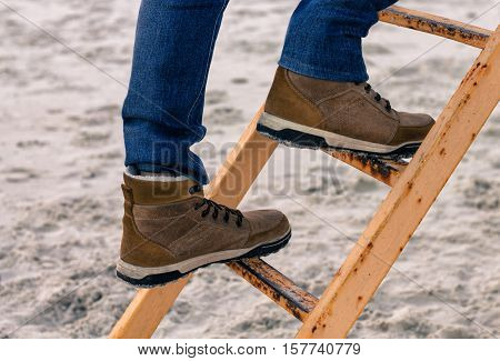 Man's foot climbing metal stairs. Sand on background