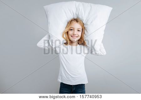 Time for rest. Joyful delighted little girl holding pillow and smiling while standing isolated on grey background