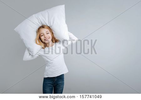 Happy child. Positive delighted cute little girl holding pillow and closing her eyes while going to sleep