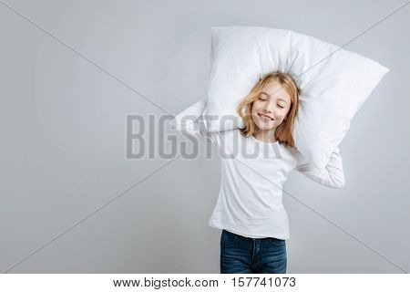 Sincere emotions. Cheerful content cute little girl holding pillow and going to sleep while standing isolated on grey background