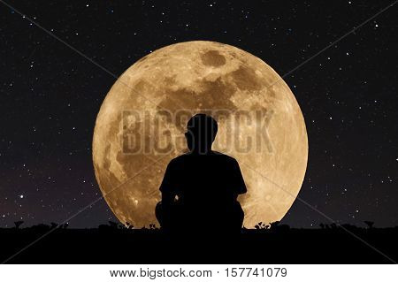 Silhouette a man sitting relaxing under full moon at night with stars on the sky. Elements of this image furnished by NASA