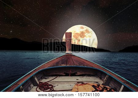 Traveling on wooden boat at night with full moon and stars on sky. romantic and scenic panorama with full moon on sea at night. Elements of this image furnished by NASA