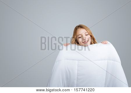 Warm and cosy. Positive content smiling girl covering with blanket and smiling while pretending to sleep