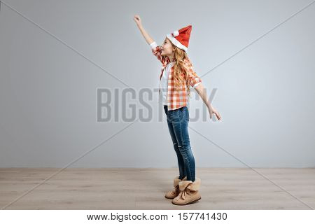 To the rescue. Ceerful little cute girl holding hand up and smiling while standing half turned isolated on grey background
