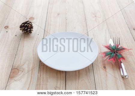 christmas dinner table : empty white dish and fork knife on wood table