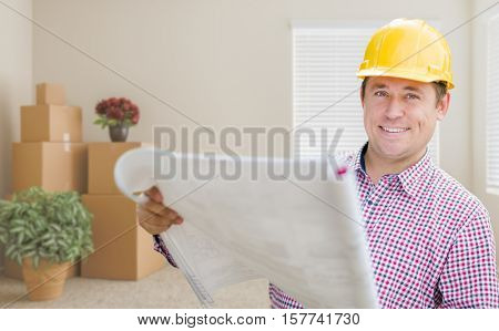 Happy Male Construction Worker In Room With Moving Boxes Holding Roll of Blueprints.